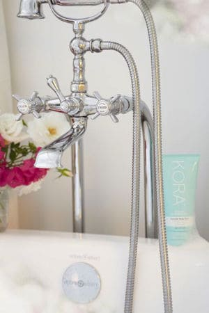 Beautiful french inspired bath taps, Kora Organics Essential Body Wash and flowers create a romantic bathroom retreat.