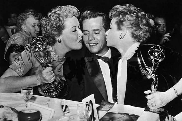 Vivian vance and lucille ball plant a kiss on producer/co-star desi arnaz at the emmy's in 1954